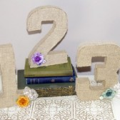Burlap covered table numbers with lace and flower accents