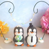 Penguin cake topper with floral arc