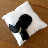 White satin ring pillow with black satin rosette