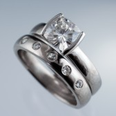 http://nodeform.com/collections/moissanite-rings/products/bridal-set-cushion-moissanite-ring-modified-tension-engagement-and-wedding-ring