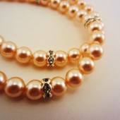 Double strand pearl bracelet with rhinestone spacers. Peach, pale pink pearls.