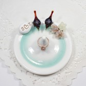 Purple love birds ring holder with blush and ivory flower bouquet