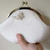 White textured silk clutch with rhinestone brooch