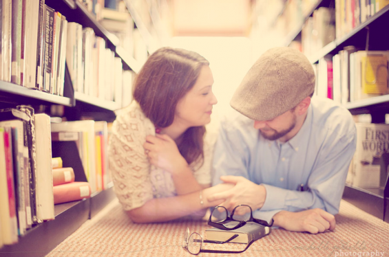 couple holding hands in library engagement shoot