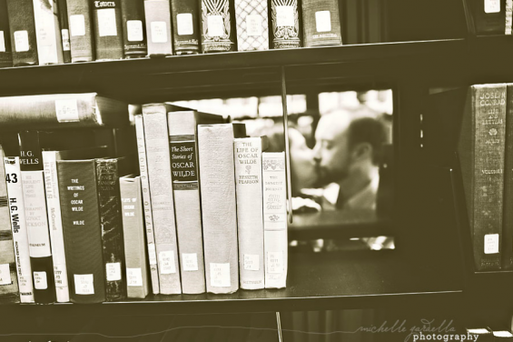 couple kissing behind books bw