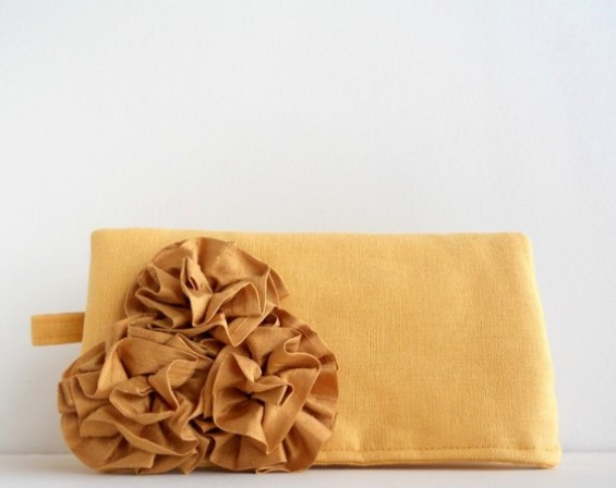 yellow clutch purse with rosettes on front