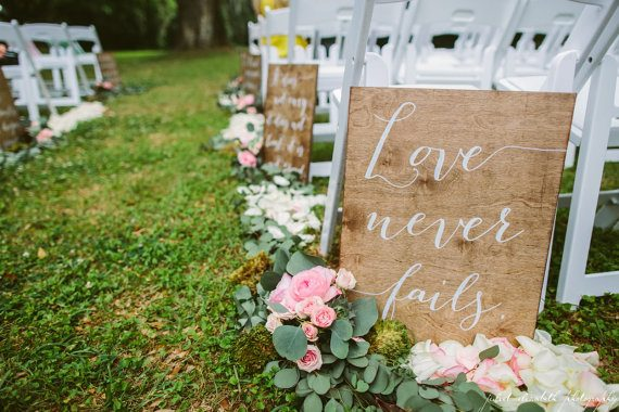 Love never fails ceremony aisle signs by Paper and Pine Co | via Wood Themed Wedding Ideas: http://emmalinebride.com/themes/wood-themed-wedding-ideas/