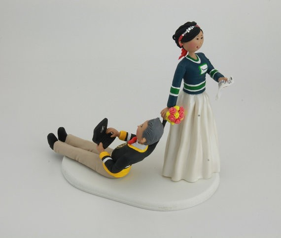 bride dragging groom hockey jerseys laptop | figurine cake toppers that look like you | by artifice producciones | https://emmalinebride.com/reception/figurine-cake-toppers/