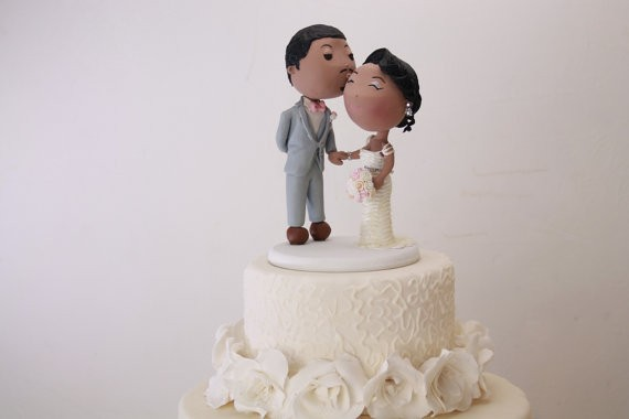groom kisses bride on cheek cake topper | figurine cake toppers that look like you | by artifice producciones | https://emmalinebride.com/reception/figurine-cake-toppers/