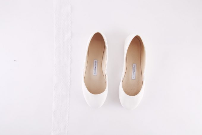 White Ballet Flats by The White Ribbon | 21 Wedding Flats That Will Look Beautiful for the Bride - https://emmalinebride.com/bride/wedding-flats-bride/