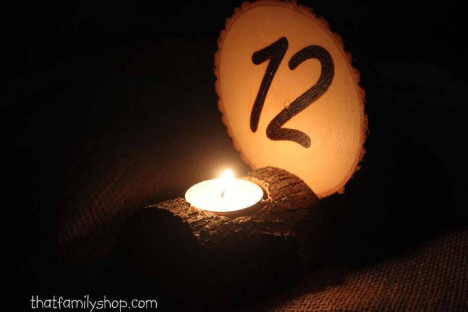 wood slice table number with candle holder lit up at night