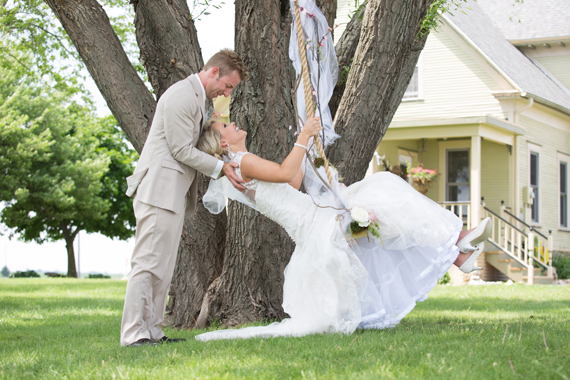 KimAnne Photography - iowa backyard wedding - groom-pushes-bride-on-swing