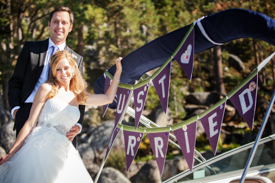 Johnstone Studios - lake tahoe wedding - bride and groom on the boat with just married purple bunting