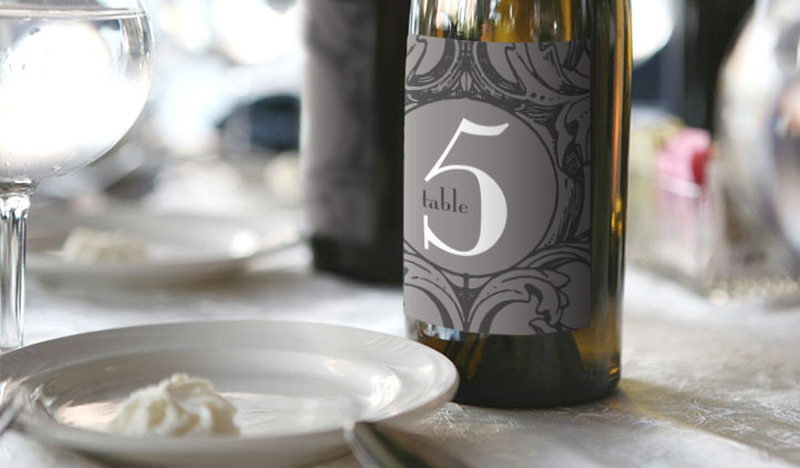 use a bottle of wine and these wedding wine labels as a table number at your reception. guests can find their table and sip on your favorite wine choices all in one! via emmalinebride.com