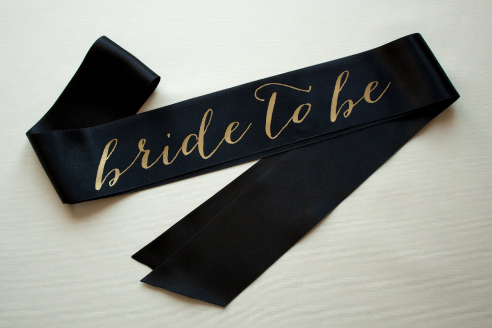 black bride to be sash with gold | stylish bachelorette sash ideas | via http://emmalinebride.com/bride/bachelorette-sash-ideas/