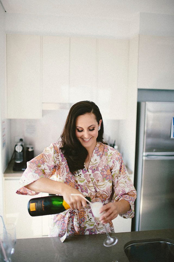 bridesmaid pouring champagne robe