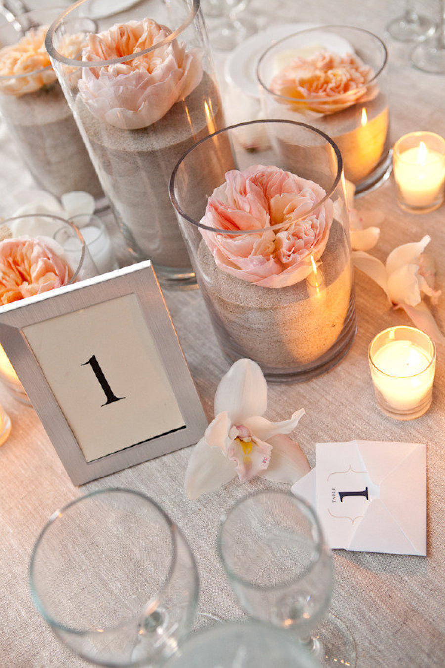 sand in votive candle holders | photo: tory williams | via decorate for beach wedding ideas from emmalinebride.com