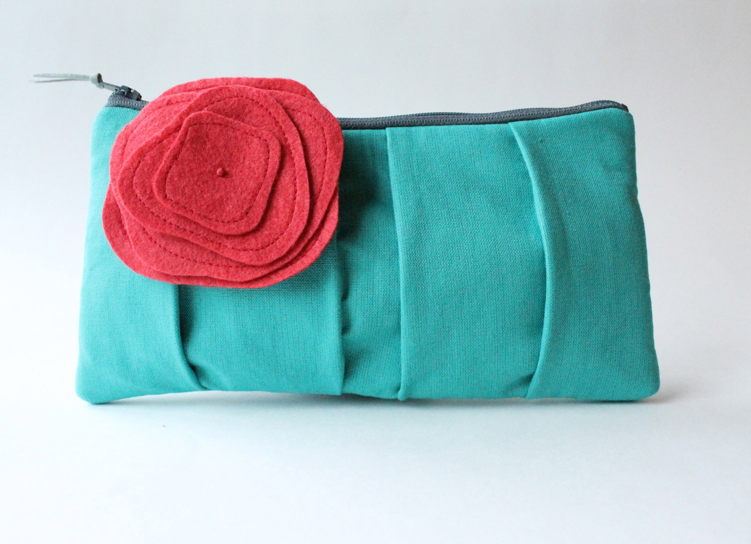 teal clutch purse with coral brooch pin flower | 7 Spring Wedding Clutches Your Girls Will Love via emmalinebride.com