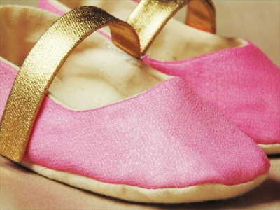 up close of hot pink and gold flower girl shoes